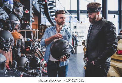 Two men in motorcycle shop. Customer and salesman.Shop assistant is helping bearded man in choosing new vehicle, motorcycle accessories and other biker stuff. Buying new helmet. Safety driving concept