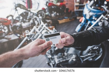 Two men in motorcycle shop. Customer and salesman. Shop assistant is helping bearded man in choosing new vehicle, motorcycle accessories and other biker stuff. Giving credit card while buying.