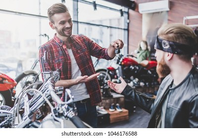 Two men in motorcycle shop. Customer and salesman. Shop assistant is helping bearded man in choosing new vehicle, motorcycle accessories and other biker stuff. Giving keys to new owner.