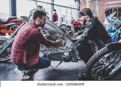 Two men in motorcycle shop. Customer and salesman. Shop assistant is helping bearded man in choosing new vehicle, motorcycle accessories and other biker stuff.