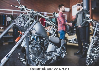 Two men in motorcycle shop are shaking hands. Customer and salesman. Shop assistant is helping bearded man in choosing new vehicle, motorcycle accessories and other biker stuff.
