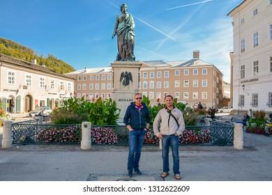 Two men near Wolfgang Amadeus Mozart monument statue at Mozartplatz square in Salzburg, Austria. Salzburg is on banks of River Salzach, at northern boundary of Alps. Salzburg, Austria - September 2018