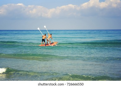 two men on a boat in the sea are beautiful with a bare torso rowing from the shore
