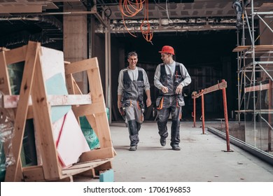 Two men on a construction site walking and talking and finishing work going home