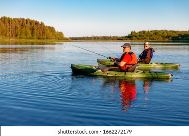 Two men on kayaks fish in sunny weather on a lake
