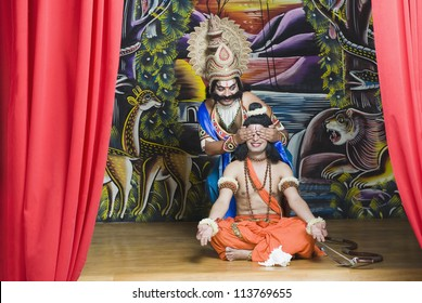 Two men on stage dressed-up as Rama and Ravana the Hindu mythological characters