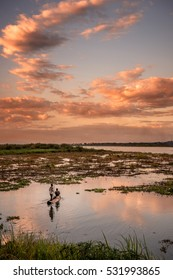Two men out in a traditional canoe fishing at sunset in Africa