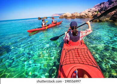 Two men paddle a kayak on the sea. Kayaking on island