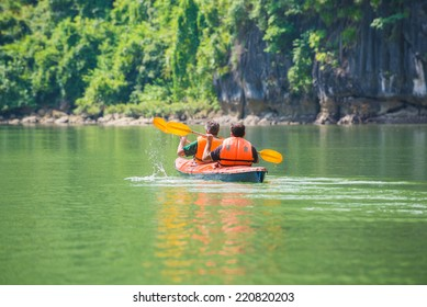 Two men paddle a kayak on the sea. Kayaking in Ha Long Bay