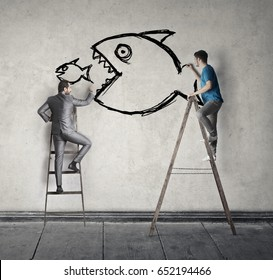 Two men painting on the wall a big fish eating a smaller one