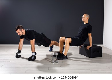 Two men  perform fitness training in the gym,push ups with boxing gloves,exercise of strength and flexibility