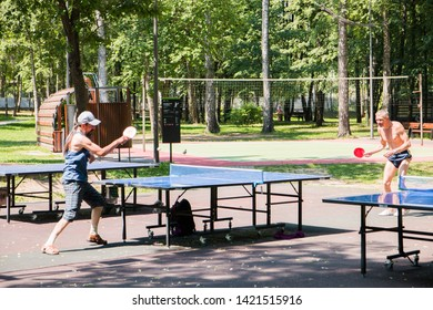 Two men play table tennis on the Playground in the Park in the summer, Moscow, Russia, June 2019