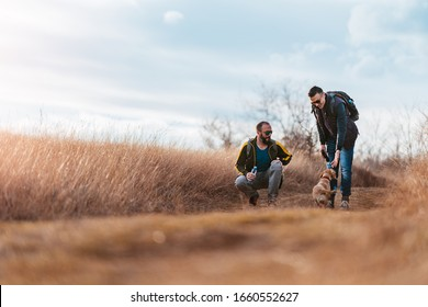 Two men play with their dog