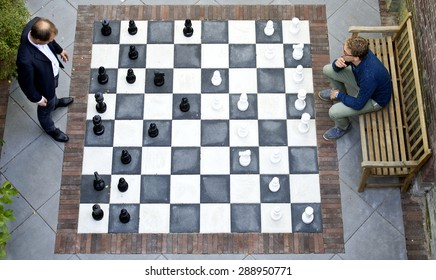 Two men playing a game of outdoor chess with large pieces, seen from above