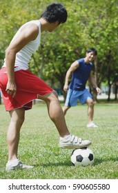 Two men playing soccer in park