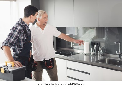 Two men of plumbers are standing in the kitchen and inspecting the future site for repair work. They stand near the sink. Next to them on the desk is a black tool box.