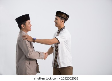 Two men pose in front of the camera. embracing each other during eid mubarak celebration