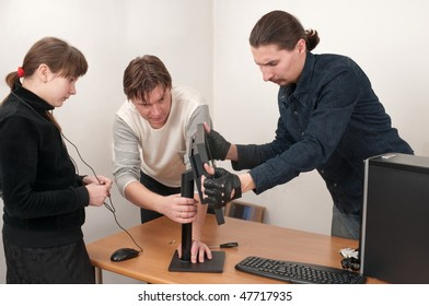 Two men prepare the computer for connection, and the girl observes. A family.