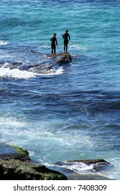 Two men preparing to enter the water at the rock edge