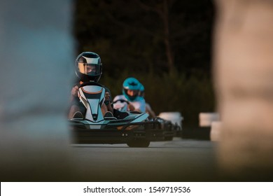 Two men are racing in commercial amateur gokart race on a closed circuit. Fun leisure racing activity, go kart trophy between friends.