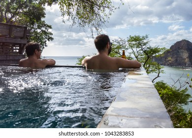 two men relaxing in a peaceful pool overlooking the pacific ocean in Nicaragua
