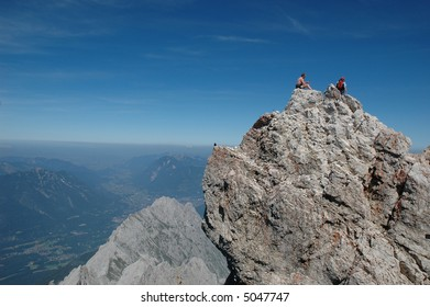 Two men resting and enjoying the view from the top of a mountain peak they have climbeed