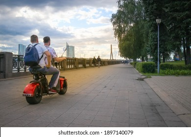 two men ride an electric scooter along the city embankment on summer day, everyday environmentally friendly transport for commuting, recreation and entertainment