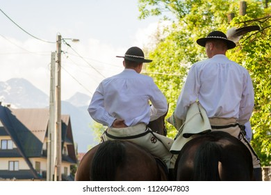Two men riding horses. People dressed in folk costumes. White shirts, hat with a feather. The tradition of Polish mountains in Zakopane. 27/05/2018 - Zakopane, Poland