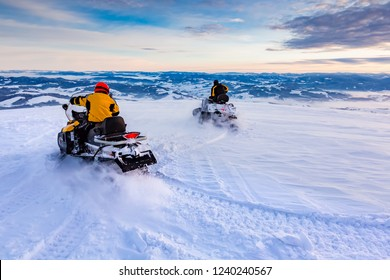 Two men are riding snowmobile in mountains. Beautiful morning light. Blue shadows.