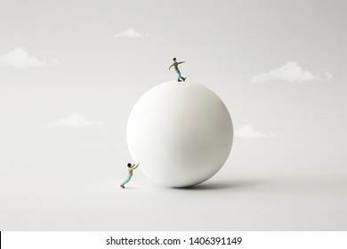 two men rolling big sphere, surreal concept