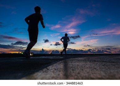 Two men running on oil rig helipad in Gulf of Thailand in sunset time with helipad light on