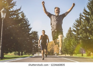 The two men running on the road in the park on the sunny background