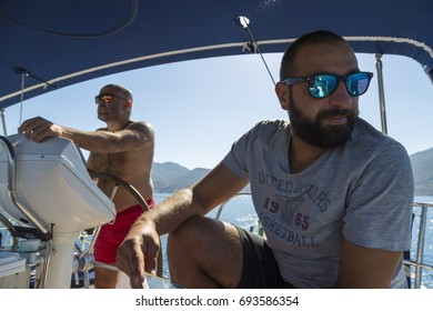 Two men sailing on the boat. One has grey top and black bottom with blue sunglasses. The other has only a red short with yellow sunglasses.