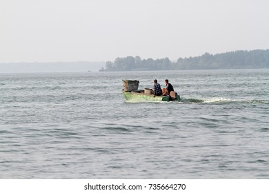 Two men are sailing on an old motor boat. Social problems illegal fishing and border crossing.