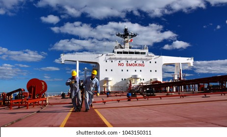 Two men (sailors) are working on deck of supertanker