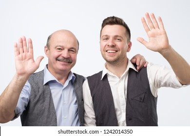 Two men saying hello, waving a hand. Welcome home sign