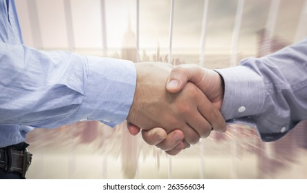 Two men shaking hands against room with large window looking on city
