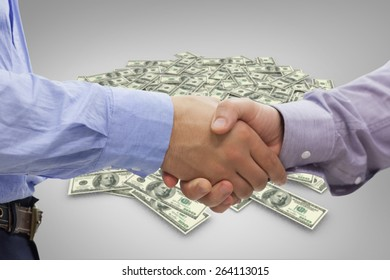 Two men shaking hands against pile of dollars