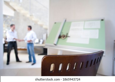 Two men shaking hands with blue prints on the drafting board with selective focus on a chair in the foreground