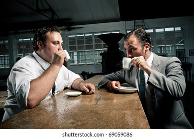 two men share some coffee and look at each other while drinking