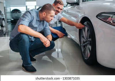 Two men sit in squad position and look at wheel of white car. Berded guy points on top of wheel. He looks at other man and smile. Serious man looks as well. He is concentrated.