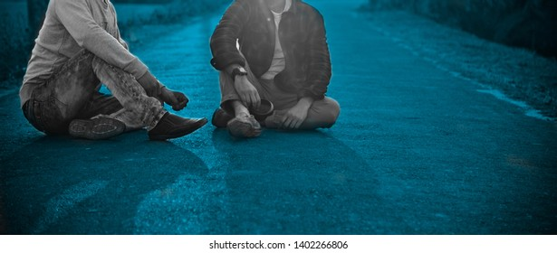 Two men sitting on an empty blue street isolated unique photo
