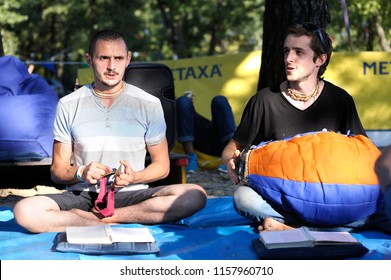 "Two men sitting on a ground and playing oriental musical instruments. Fest of Yoga and Vedic Culture ""Vedalife-2018"". July 25, 2018. Kiev, Ukraine"