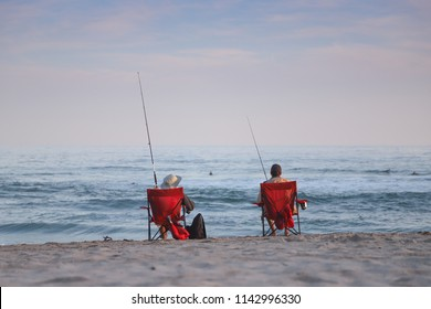 Two men sitting on red beach chairs catching fish together