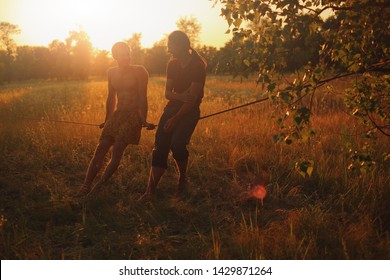 Two men sitting on slackline in the meadow at sunset.