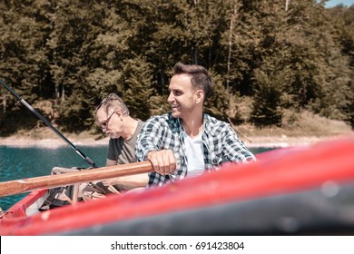 Two men sitting in rowboat and catching fish
