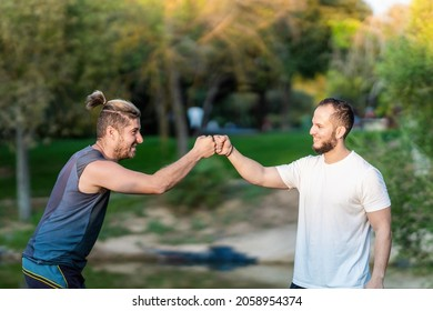 Two men in sportswear clashing fists in a park gesturing being a team