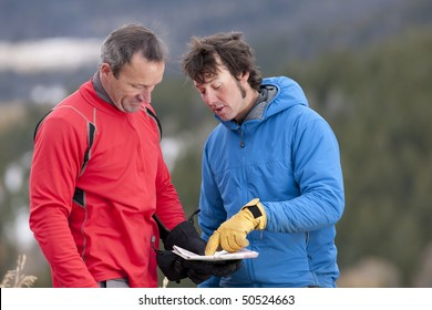 Two men stand and look down at a map together in the wilderness. One man is pointing at a spot on the map and talking. Horizontal format.