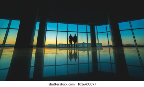 The two men stand on the panoramic window background