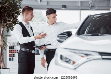 Two men stand in the showroom against cars. Close-up of a sales manager in a suit that sells a car to a customer.